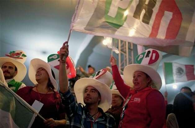 Supporters of Enrique Pena Nieto, presidential candidate for the Revolutionary Institutional Party (PRI) gather at party headquarters as exit polls begin to come in for general elections in Mexico City, Mexico, Sunday, July 1, 2012. Pena Nieto is leading Mexico's elections with about 40 percent of the vote, exit polls showed Sunday, signaling a return of his long-ruling party to power after a 12-year hiatus. (AP Photo/Alexandre Meneghini) Photo: Alexandre Meneghini, Associated Press / AP
