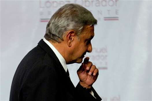 Presidential candidate Andres Manuel Lopez Obrador of the Democratic Revolution Party (PRD) leaves the podium after speaking in Mexico City, Sunday, July 1, 2012. Obrador said he won't concede the presidency despite an official preliminary count that shows him losing to former ruling party candidate Enrique Pena Nieto, of the Institutional Revolutionary Party (PRI), and that he would wait for a full count. (AP Photo/Eduardo Verdugo) Photo: Eduardo Verdugo, Associated Press / AP2012