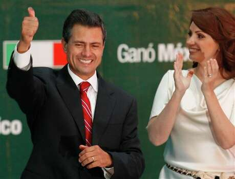Presidential candidate Enrique Pena Nieto gestures to supporters next to his wife Angelica Rivera at his party's headquarters in Mexico City, early Monday, July 2, 2012. Mexico's federal elections institute's preliminary count says Pena Nieto has won the presidency. The candidate for the old-ruling Institutional Revolutionary Party, or PRI, has won about 38 percent of the vote according a representative count of the ballots.  (AP Photo/Marco Ugarte) Photo: Marco Ugarte, Associated Press / AP