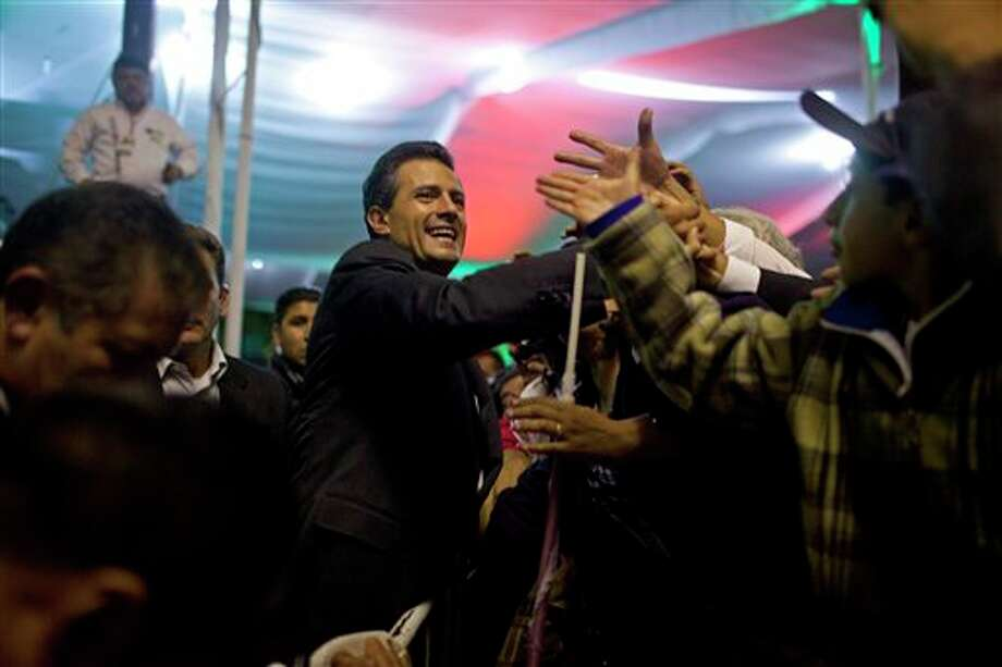 Enrique Pena Nieto, presidential candidate for the Revolutionary Institutional Party (PRI), center, greets supporters at the party's headquarters in Mexico City, early Monday July 2, 2012. Mexico's old guard sailed back into power after a 12-year hiatus Sunday as the official preliminary vote count handed a victory to Pena Nieto, whose party was long accused of ruling the country through corruption and patronage. (AP Photo/Alexandre Meneghini) Photo: Alexandre Meneghini, Associated Press / AP