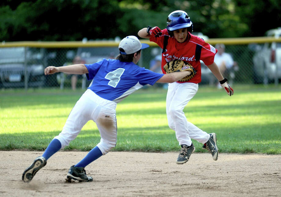Stamford's Mark Raimondi is tagged out by Darien's Ethan Ehlers during Friday's Little League game at McGuane Field in Darien on June 29, 2012. Photo: Lindsay Niegelberg / Stamford Advocate