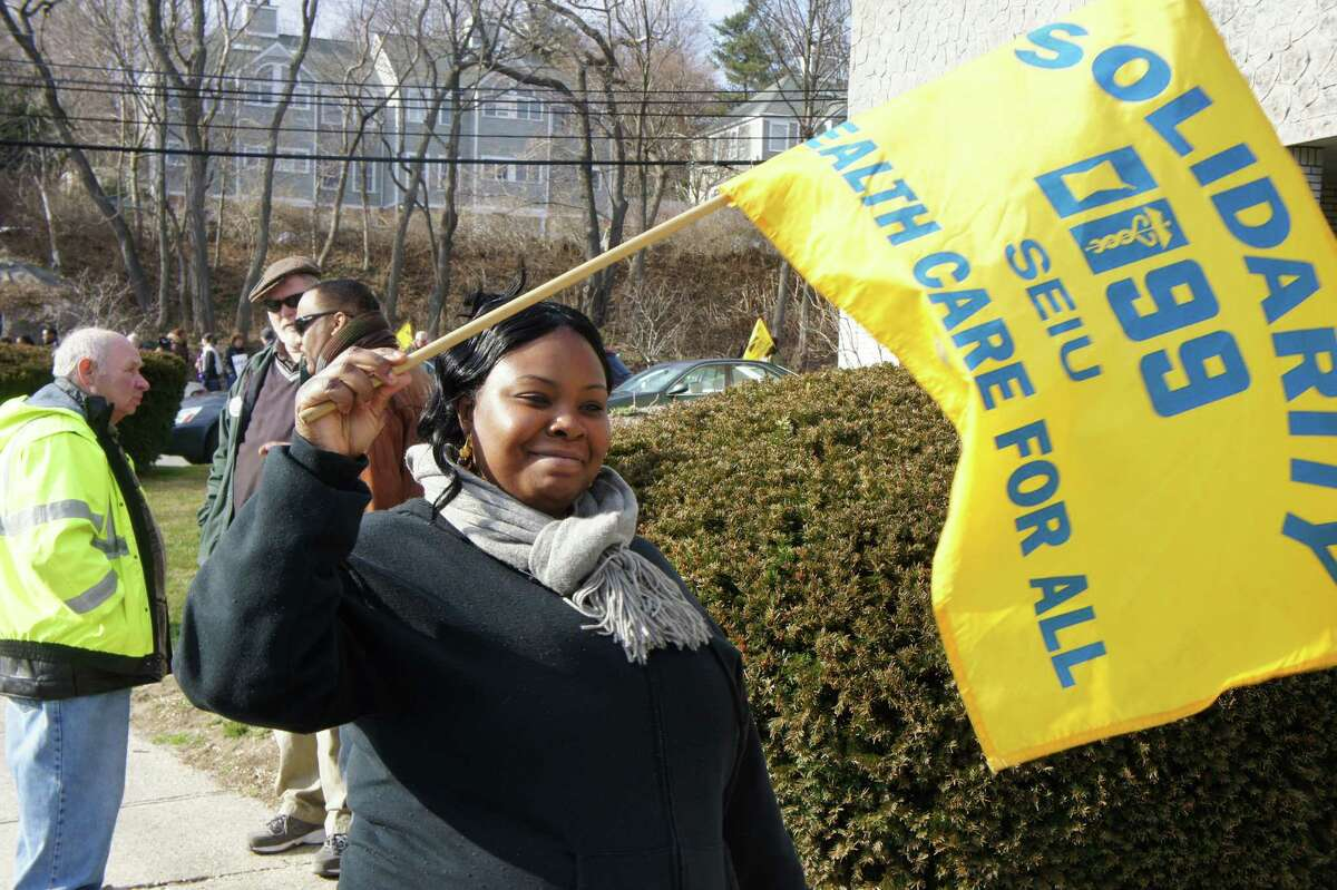 Westport Health Care Center certified nursing assistant Tina McCoy joins other members of New England Health Care Employees Union, District 1199, picket Friday outside the Westport Health Care Center to protest impasse in negotiating a new contract with HealthBridge, the company that manages the nursing home.