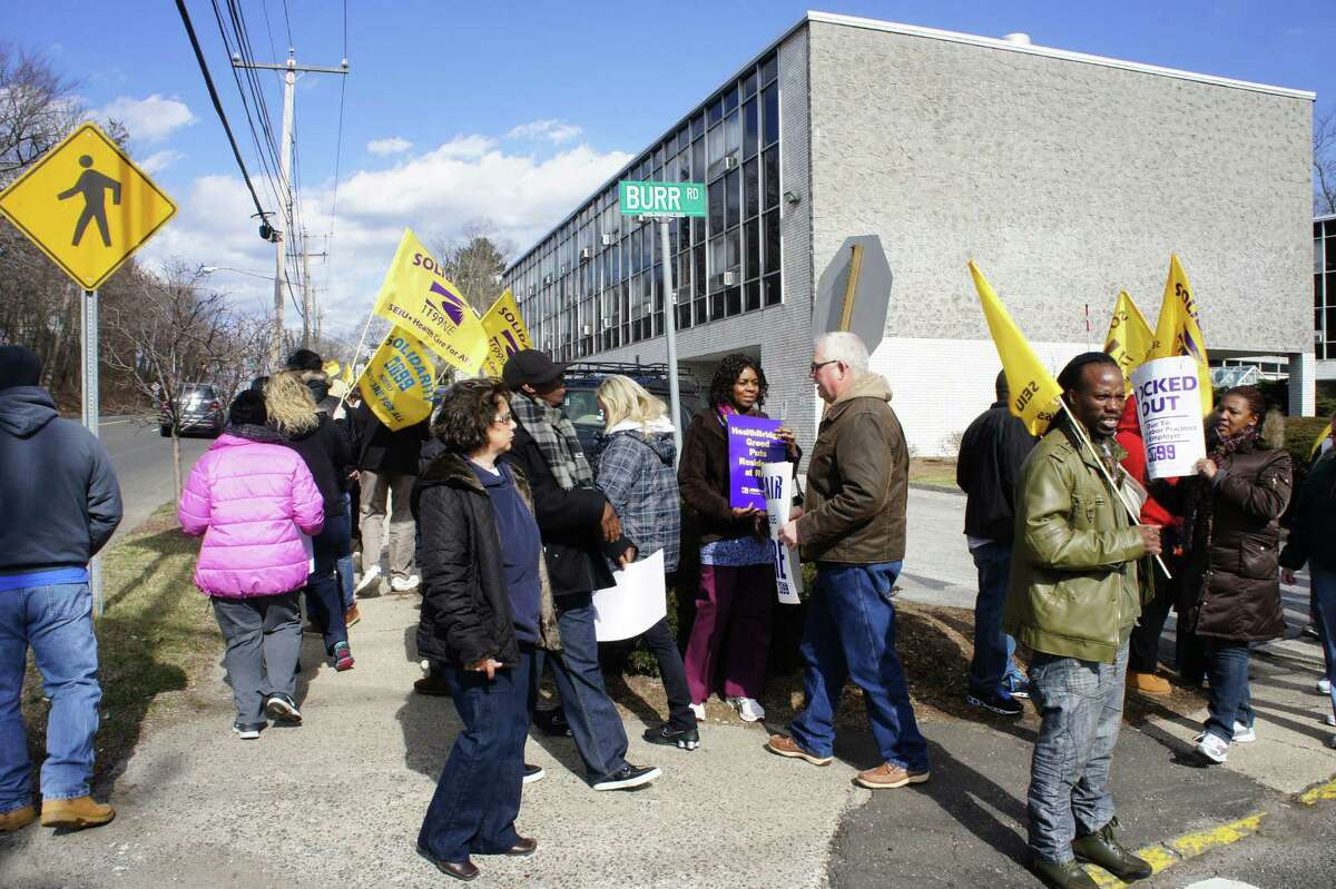 Members of New England Health Care Employees Union, District 1199, picket Friday outside the Westport Health Care Center to protest impasse in negotiating a new contract with HealthBridge, the company that manages the nursing home.