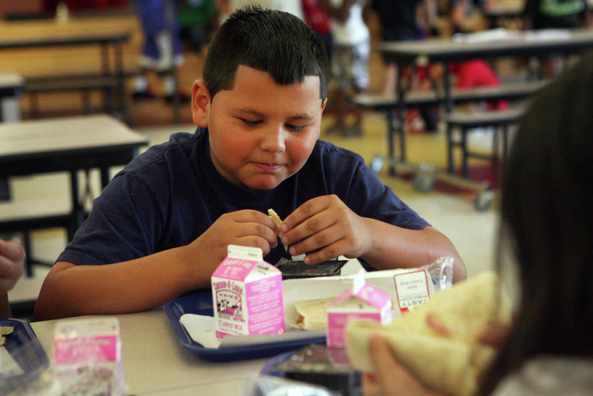 Lewis Colon, 9, eats lunch at Cesar Batalla School in Bridgeport, Conn. on Monday, July 2, 2012. The lunch is part of the Seamless Summer Meals program offered in 82 sites around Bridgeport. Any child under 18 years of age can walk in and have breakfast and lunch. Colon takes part in the Early Reading Success program at the school.