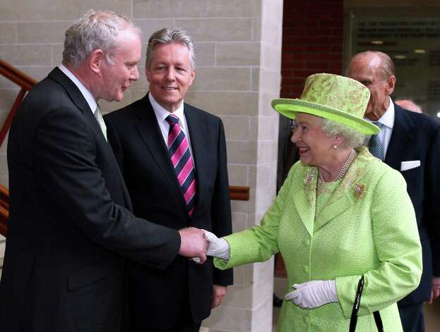 Britain's Queen Elizabeth II shakes hands with Northern Ireland Deputy First Minister and former IRA commander Martin McGuinness watched by First minister Peter Robinson, centre, at the Lyric Theatre in Belfast, Northern Ireland, Wednesday, June 27, 2012. (AP Photo/Paul Faith/pool) Photo: Paul Faith, ASSOCIATED PRESS / AP2012