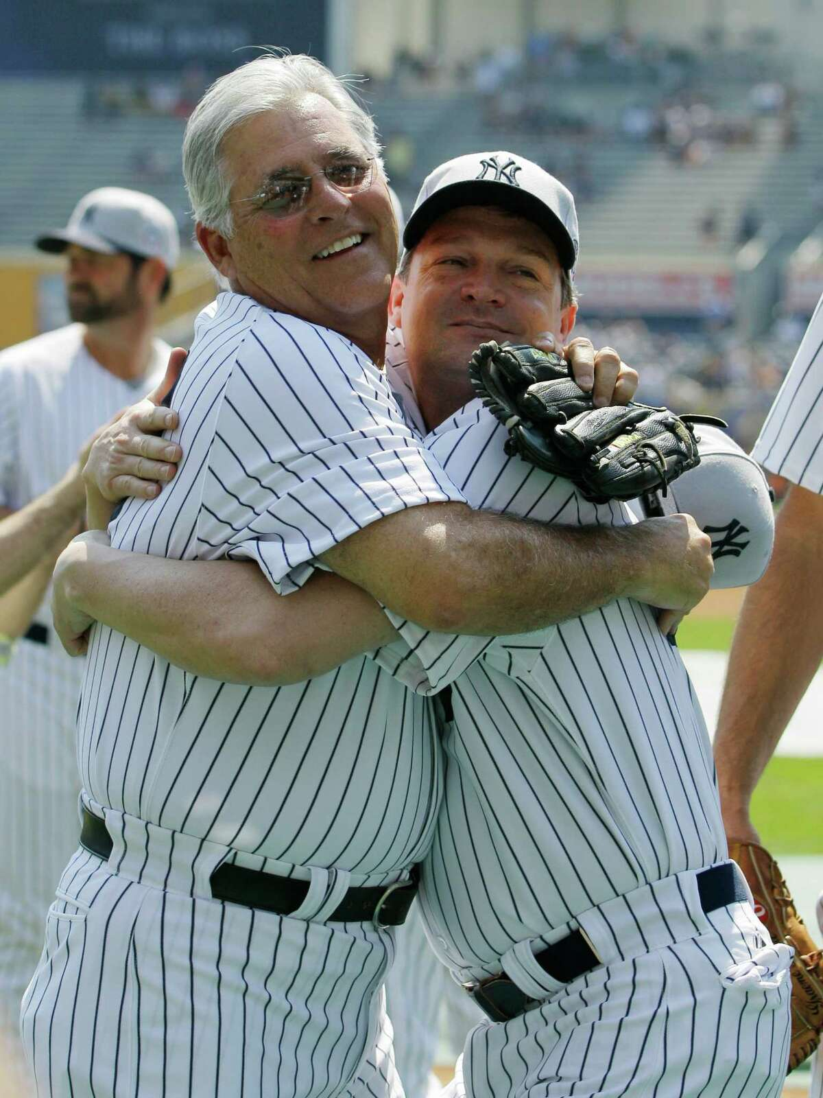 Former New York Yankees player Bucky Dent, left, and Pat Kelly embrace during Yankees Old Timers Day at Yankee Stadium in New York, Sunday, July 1, 2012.