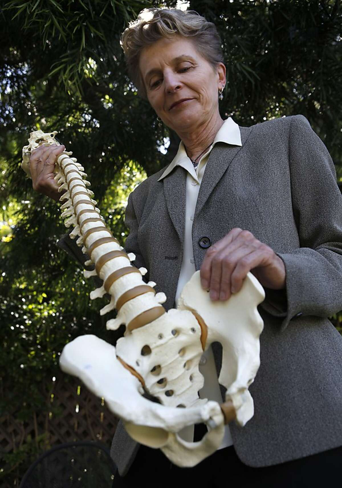 Chiropractor Lani Simpson examines a replica of a human spine and pelvic bone at her home in Berkeley, Calif. on Thursday, June 7, 2012. Simpson is a leading expert on osteoporosis, a condition which causes bones to become brittle and fragile.