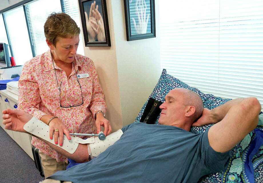 During a therapy session at Coastal Hand Therapy in Nowralk, CT on Monday July 2nd, 2012, certified hand therapist, Lisa Maggiore shows Stamford Police officer Troy Strauser how a new brace she devised will work. The brace will passively apply pressure to increase the range in which he can extend his arm. Officer Strauser was injured while chasing a robbery suspect this past May. Photo: Mark Conrad / Stamford Advocate Freelance