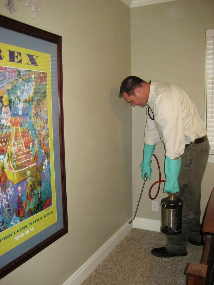 Jan Peterson of HomeTeam Pest Defense treats a home with a pest control solution. Photo: Jenny Halpin / For North Central News
