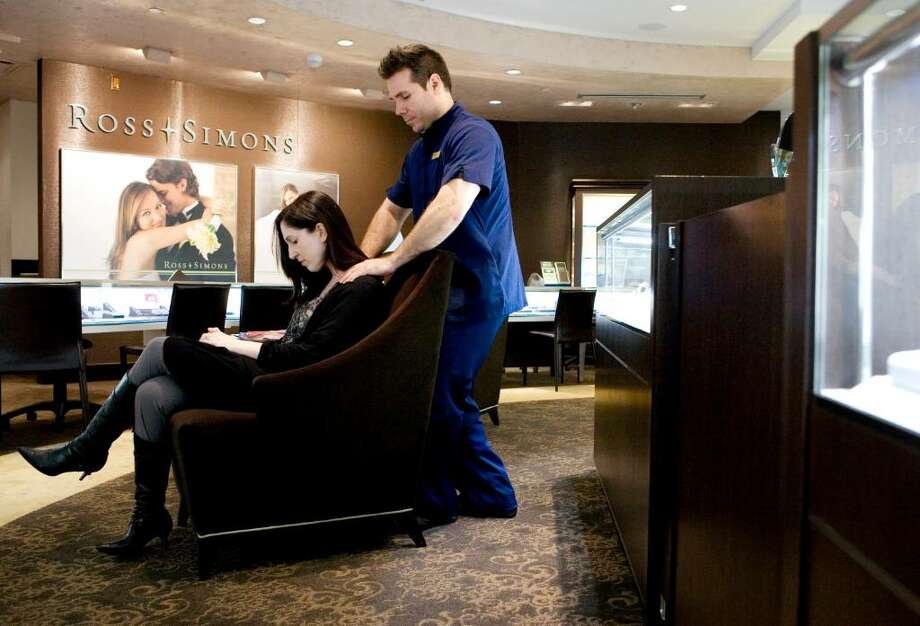 Dana Corelli, a sales associate at Ross Simons jewelry store, right, gets a massage from Mark Cuventas from the Agora Spa during a break in her shift. Massages were given to some of the 250 employees working in the mall stores to help get them through Black Friday. Photo: Kerry Sherck / Stamford Advocate Freelance