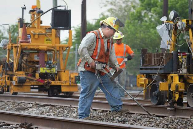 Frank Martinez, a track man uses a rail lift to replace rail road ties with other workers at the 7600 block of Avenue P, Thursday, June 28, 2012, in Houston. Union Pacific has spent $17 million replacing about 100,000 ties. Photo: Nick De La Torre, Houston Chronicle / © 2012  Houston Chronicle