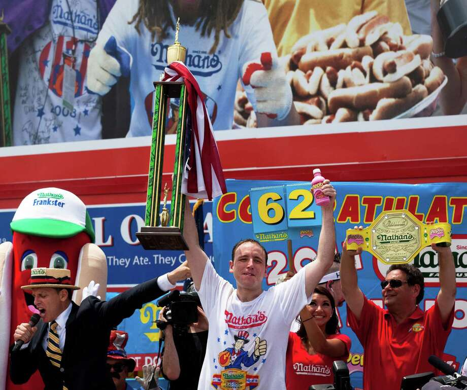 With his trophy in one hand and a bottle of Pepto-Bismol in the other, Joey Chestnut, center, accepts his trophy after winning his fifth Nathan's Famous Hot Dog Eating World Championship in 2011. He ate 62 hot dogs and buns. Photo: John Minchillo / FRE 170537