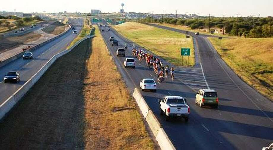 Cycylists have a police escrot as the ride on Loop 1604 in the 1604 Peleton Ride Photo: Courtesy Photo