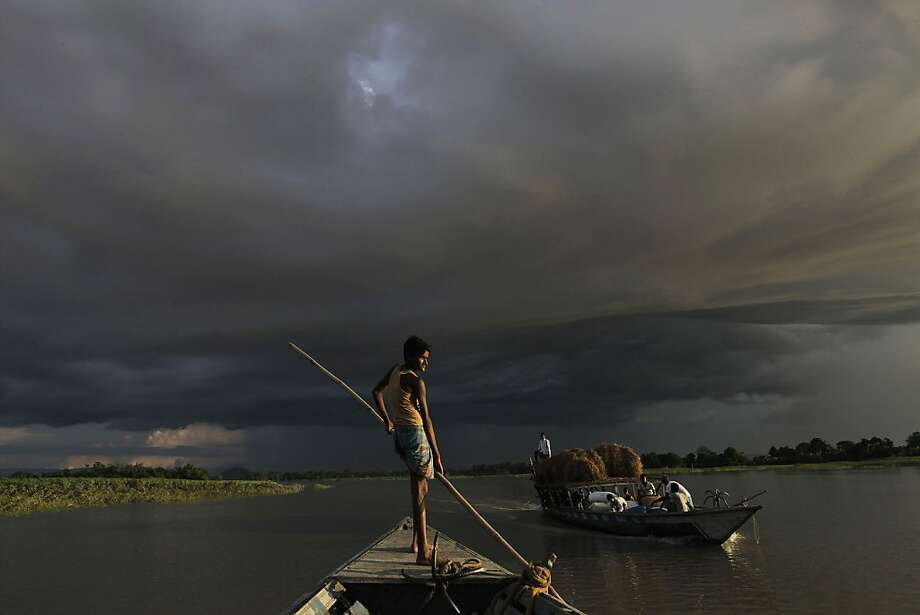 A boat carries flood relief materials as monsoon clouds surrounded the flood affected Gagalmari village in Assam state, India, Monday, July 2, 2012. The floods from monsoon rains in northeastern India killed dozens of people, with more than 2,000 villages inundated as rivers breached their banks, an official said Sunday. (AP Photo/Anupam Nath) Photo: Anupam Nath, Associated Press