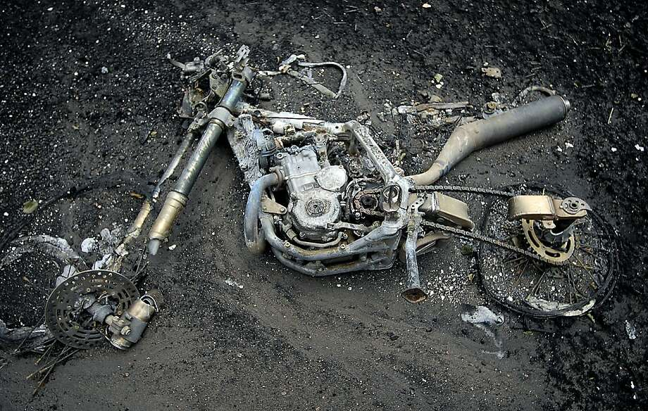 The remains of a motorcycle lies in the dirt near one of the homes destroyed by the Waldo Canyon Fire in the Mountain Shadows neighborhood of Colorado Springs, Colo., on Monday, July 2, 2012. So far, the blaze, now 45 percent contained, has damaged or destroyed nearly 350 homes. (AP Photo/Bryan Oller) Photo: Bryan Oller, Associated Press