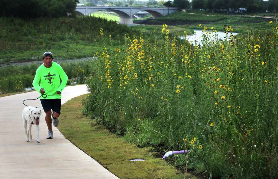 Jose Iniguez (cq) runs with his dog Luno (cq) along the recently finished Mission Reach Ecosystem Restoration and Recreation Project, an eight mile stretch of the San Antonio River, begining at Mission Rd. near Riverside Golf Course, Monday, July 2, 2012. Photo: BOB OWEN, San Antonio Express-News / © 2012 San Antonio Express-News