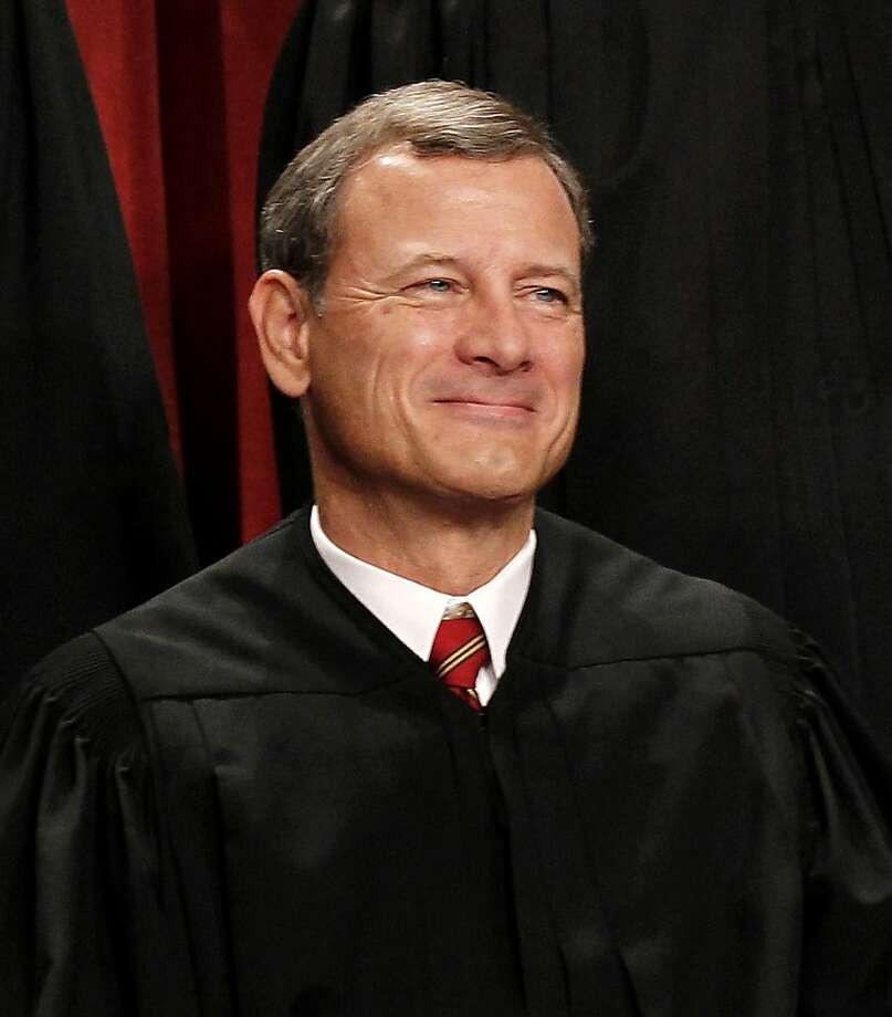 "FILE - In this Oct. 8, 2010 file photo, Chief Justice John Roberts is seen during the group portrait at the Supreme Court Building in Washington. Breaking with the court's other conservative justices, Roberts announced the judgment that allows the law to go forward with its aim of covering more than 30 million uninsured Americans. Roberts explained at length the court's view of the mandate as a valid exercise of Congress' authority to ""lay and collect taxes."" The administration estimates that roughly 4 million people will pay the penalty rather than buy insurance.  (AP Photo/Pablo Martinez Monsivais, File) Photo: Pablo Martinez Monsivais, Associated Press"
