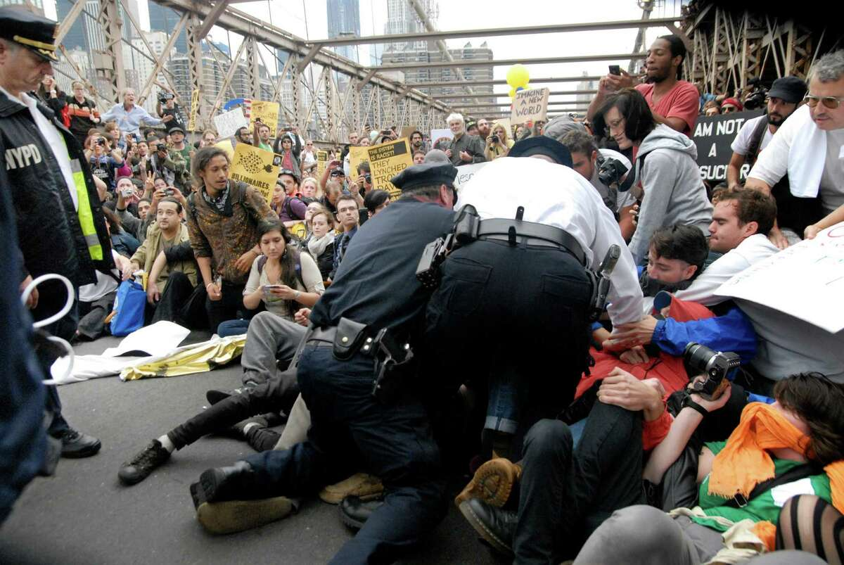 FILE - In this Oct. 1, 2011 file photo, police arrest protesters on New York's Brooklyn Bridge during march by Occupy Wall Street. A judge said in a ruling released Monday, July 2, 2012 that Twitter must give a court almost three months' worth of an Occupy Wall Street protester's tweets after prosecutors demand the messages to make a case for arrests. (AP Photo/Stephanie Keith, File)