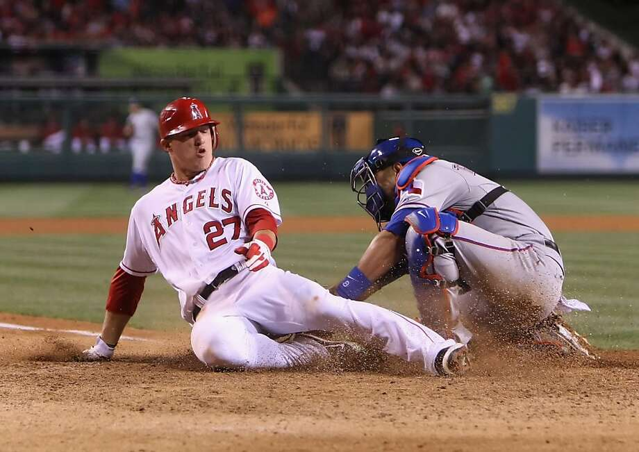 ANAHEIM, CA - JUNE 02:  Mike Trout #27 of the Los Angeles Angels of Anaheim slides safely past the tag of catcher Yorvit Torrealba #8 of the Texas Rangers in the seventh inning at Angel Stadium of Anaheim on June 2, 2012 in Anaheim, California. The Angels defeated the Rangers 3-2.  (Photo by Jeff Gross/Getty Images) Photo: Jeff Gross, Getty Images
