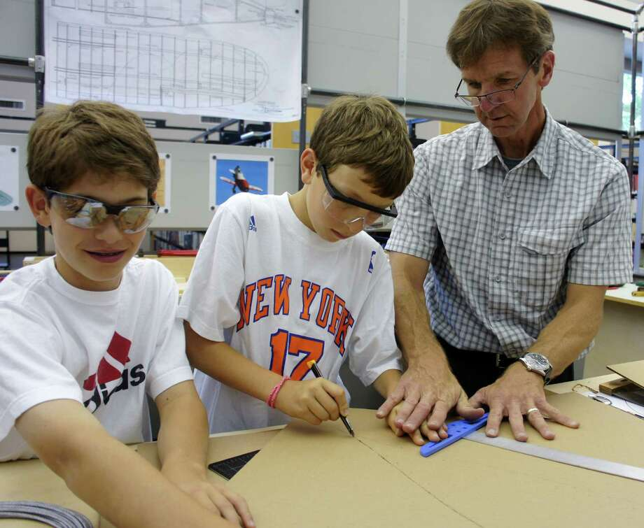 Joseph Schott, right, the Westport Public Library's new Maker-in-Residence, guides rising Bedford Middle School seventh graders Sam Greenberg, center, and David Hoffman, left as they cut out the fuselage for a cardboard model airplane in the library's new Maker Space. Photo: Paul Schott / Westport News