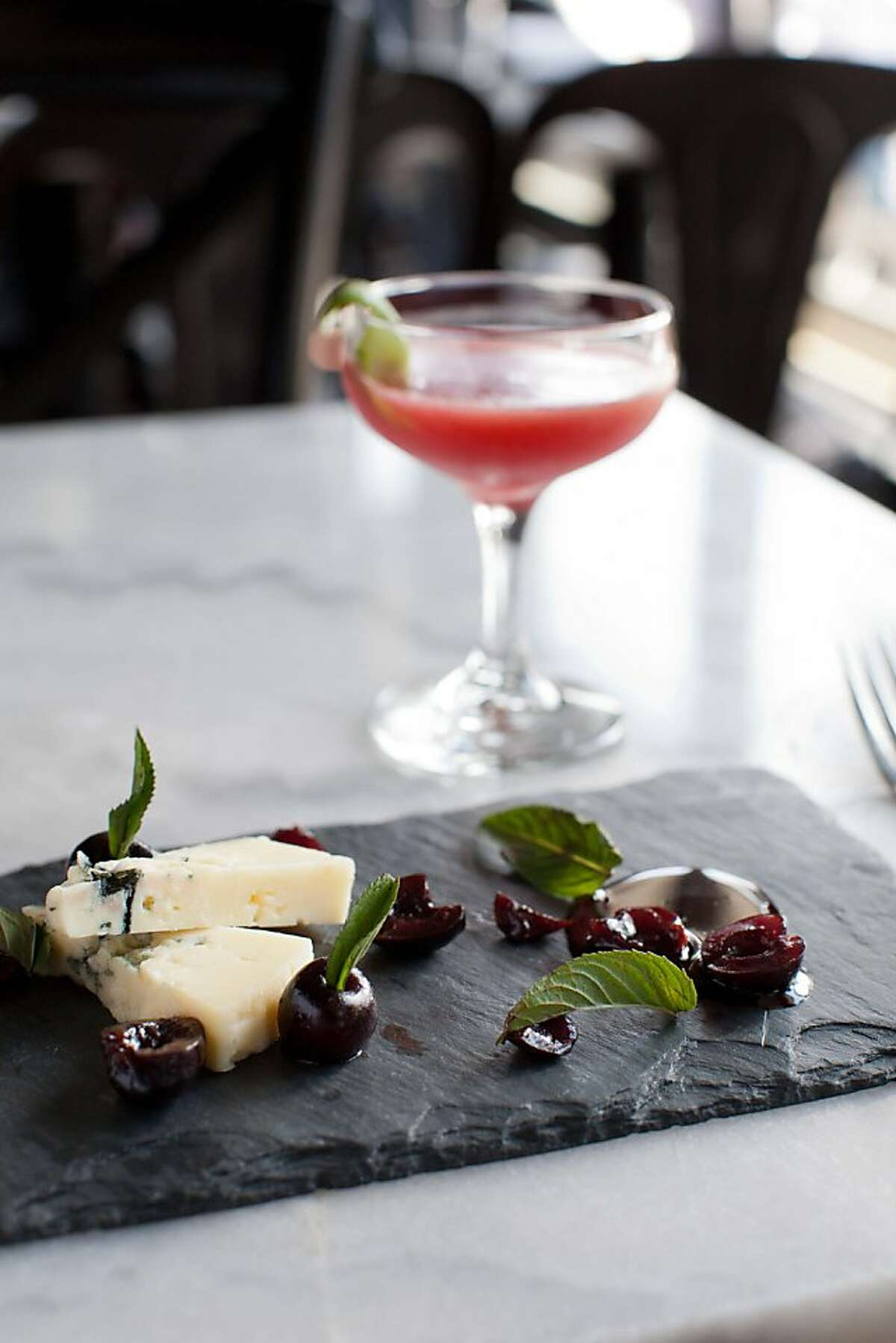 """Park Tavern restaurant's new """"Three Martini lunch and Summer Fridays"""" program features three courses, each paired with a martini-type drink, small in size so guests can indulge. Here, a dessert of Rogue Creamery blue cheese with smoked bing cherries, chocolate mint sauce and walnut bread is paired with a sour cherry daiquiri."""