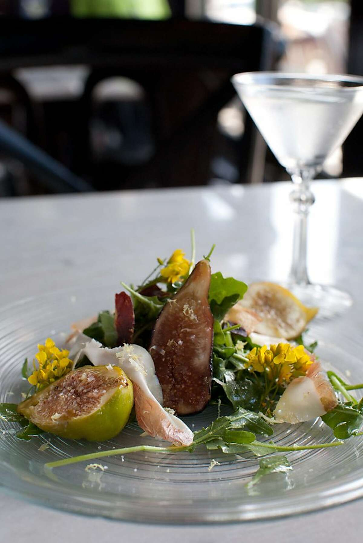 """Park Tavern's new """"Three Martini Lunch and Summer Fridays"""" features three courses, each paired with a martini-like drink. A starter salad of smoked figs, prosciutto, arugula and flowers is paired with a vodka martini spiked with black peppercorns for a palate-pleasing kick."""