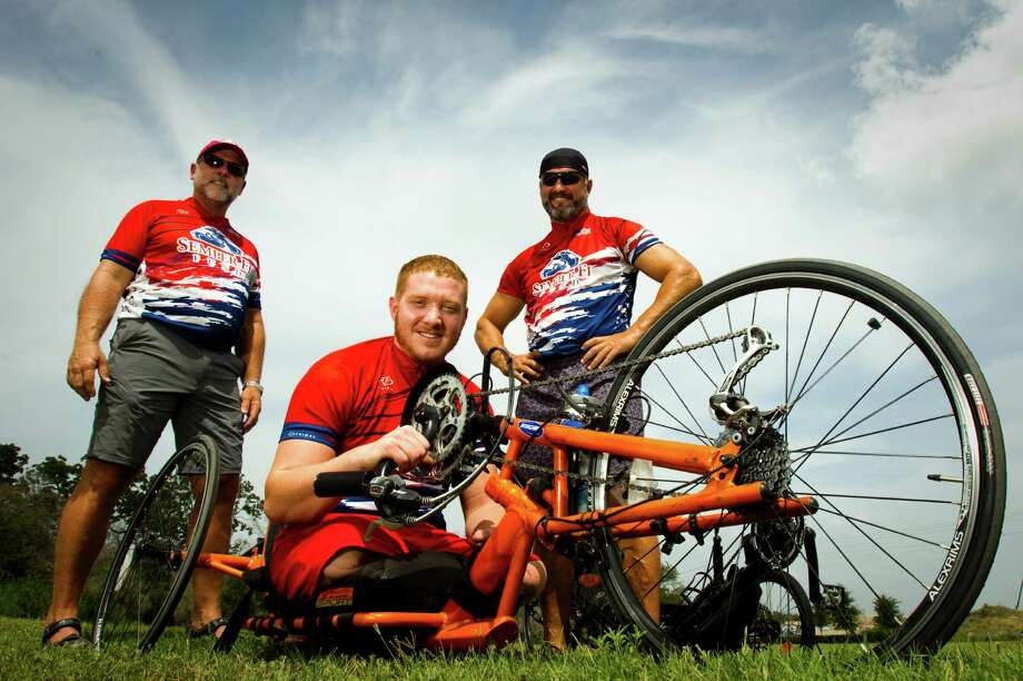 Ben Maenza, a Marine who lost his legs to an improvised bomb in Afghanistan in 2010, pauses for a photo with fellow riders Dennis McLaughlin, left, of Friendswood, and Troy McLehany, of League City. Photo: Brett Coomer / © 2012 Houston Chronicle