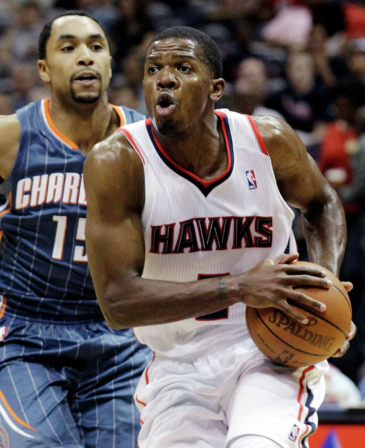 FILE - In this April 4, 2012, file photo, Atlanta Hawks' Joe Johnson, right, drives against Charlotte Bobcats' Gerald Henderson,in an NBA basketball game in Atlanta. Multiple media outlets, starting with ESPN and all citing anonymous sources, are reporting the Hawks and New Jersey Nets have agreed to a trade that would send Johnson from Atlanta to Brooklyn, Monday, July 2.