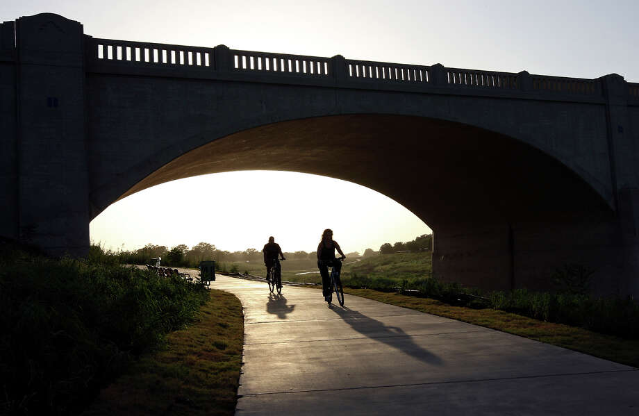 Cyclists ride under the Mrs. Frank W. Sorell Bridge (Roosevelt Ave.) on the new section of the Mission Reach Ecosystem Restoration and Recreation Project of the San Antonio River Monday, July 2, 2012. Photo: Edward A. Ornelas, San Antonio Express-News / © 2012 San Antonio Express-News