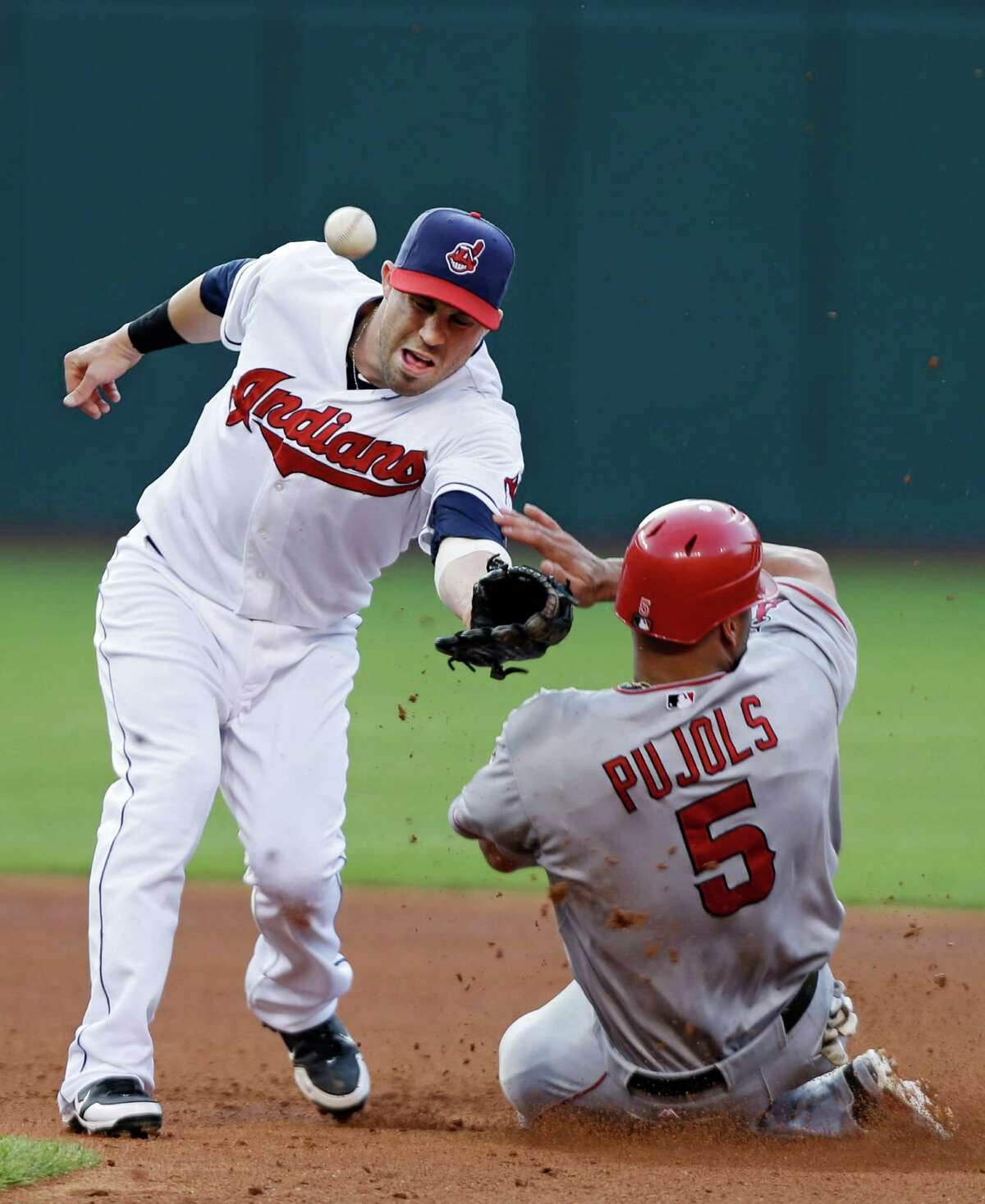 Los Angeles Angels' Albert Pujols (5) steals second base as the throw hits his shoulder and ricochets past Cleveland Indians second baseman Jason Kipnis in the fourth inning of a baseball game Monday, July 2, 2012, in Cleveland.