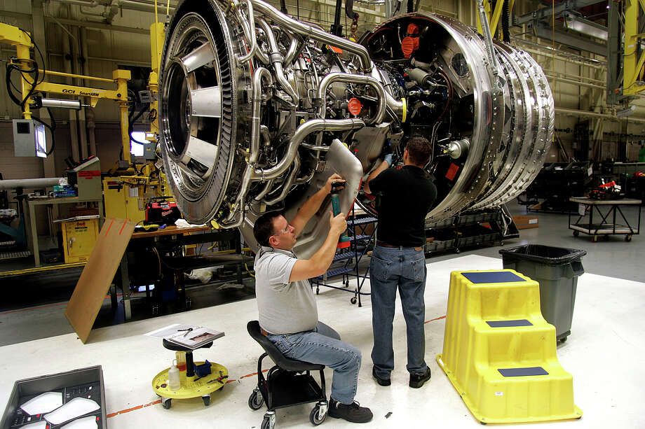 Technicians work on a General Electric Co. GE-90 jet engine at the company's Aviation Assembly & Test plant in Durham, North Carolina, U.S., on Monday, Oct. 8, 2007. General Electric Co., the world's second-biggest company by market value, said profit rose 7.1 percent in the third quarter on overseas sales of locomotives, airplane engines and turbines for power-generation plants. Photographer: Jim R. Bounds/Bloomberg News Photo: JIM R. BOUNDS, BLOOMBERG NEWS