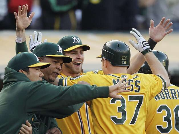 Oakland Athletics' Brandon Moss (37) is congratulated by Josh Reddick, center, after Moss hit a three-run home run off Boston Red Sox's Daisuke Matsuzaka in the second inning of a baseball game, Monday, July 2, 2012, in San Francisco. (AP Photo/Ben Margot) Photo: Ben Margot, Associated Press