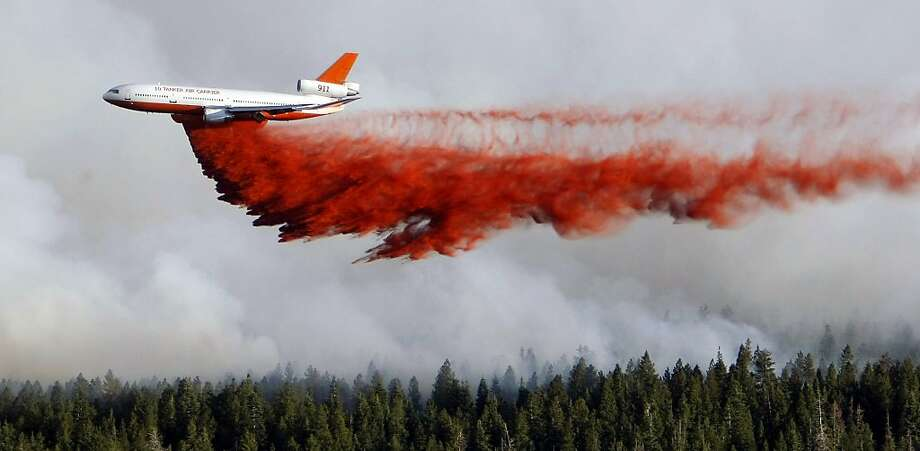 A heavy tanker drops retardant as crews battle the Shingle Fire east of Cedar City, Utah, on Monday, July 2, 2012. Evacuations were ordered as the 500-acre wildfire that broke out Sunday threatened about 100 cabins inside Dixie National Forest. In all, 10 wildfires were burning Monday across Utah. (AP Photo/The Deseret News, Scott G Winterton) Photo: Scott G Winterton, Associated Press