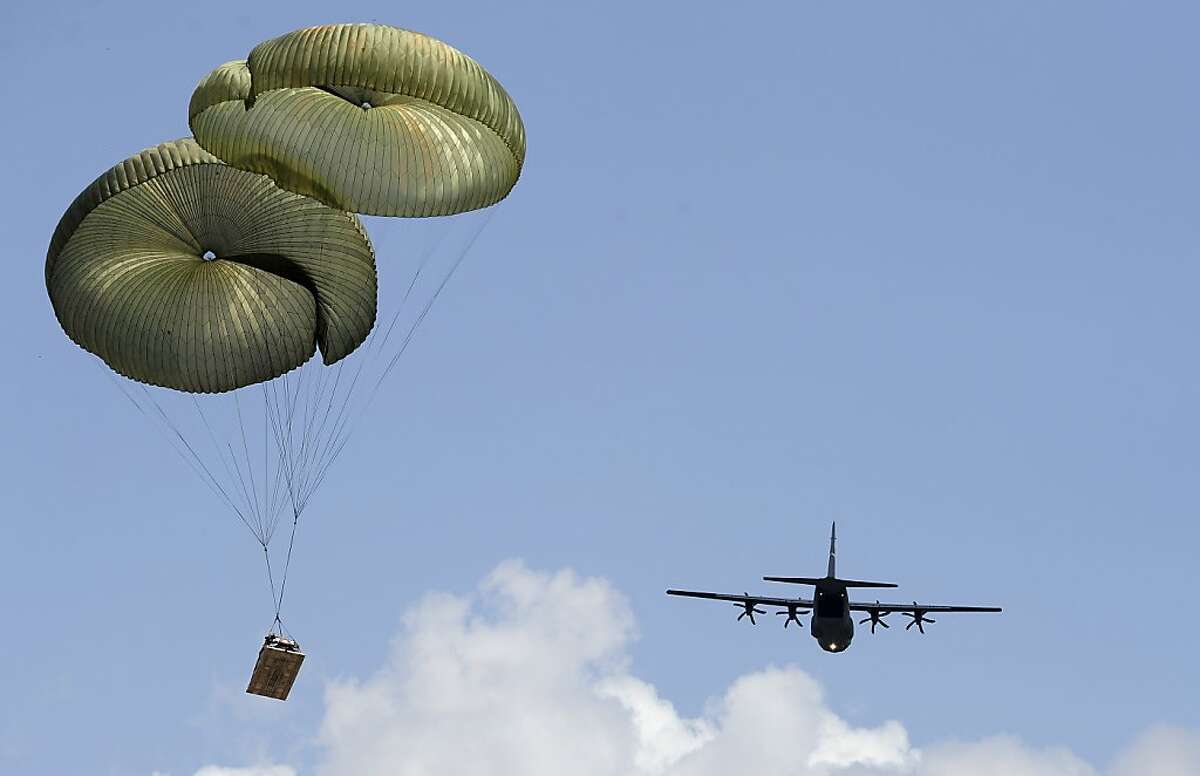 A C-130 J-model aircraft from the 317th Airlift Group at Dyess Air Force Base, near Abilene, Texas, drops a palletized Humvee vehicle during the largest ever formation flight of J-model C-130s on Monday July 2, 2012. A total of 16 aircraft took part in the formation flight and air drop. (AP Photo/Reporter-News, Greg Kendall-Ball)