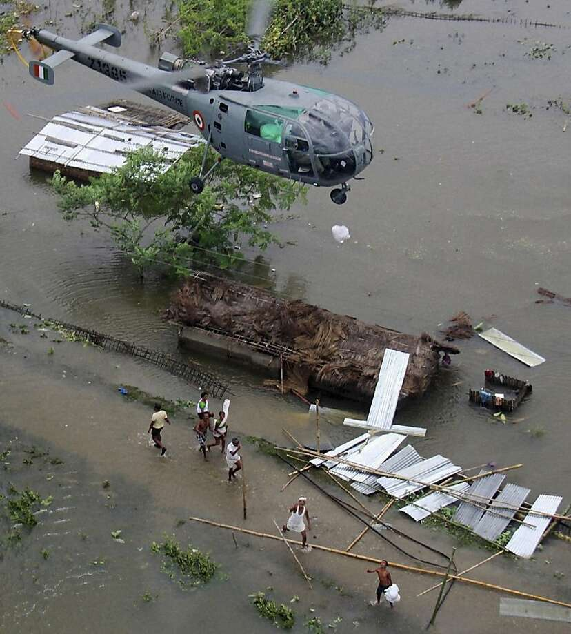 In this photo taken Sunday, July 1, 2012, flood victims rush for food packets being dropped from an Indian Air Force helicopter at a flooded area of Sonitpur in Assam state, India. The floods from monsoon rains in northeastern India killed dozens of people, with more than 2,000 villages inundated as rivers breached their banks, an official said Sunday. (AP Photo) INDIA OUT Photo: Associated Press