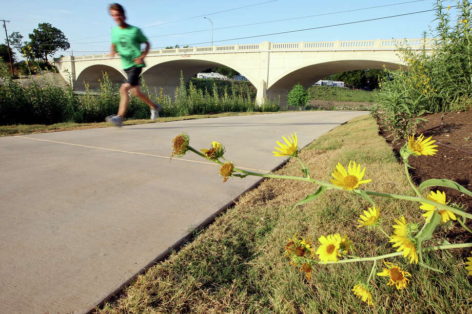 A runner passes the Mrs. Frank W. Sorell Bridge (Roosevelt Ave.) on the new section of the Mission Reach Ecosystem Restoration and Recreation Project of the San Antonio River Monday, July 2, 2012. Photo: Edward A. Ornelas, San Antonio Express-News / © 2012 San Antonio Express-News