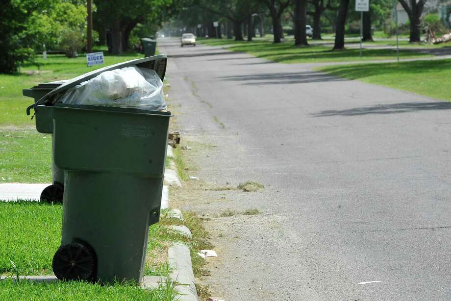 A full can waits for pickup by a city automated garbage truck along the curb Monday July 2, 2012.   The City of Port Arthur got into a situation when a lot of the city's trash trucks broke down at once. The city borrowed trucks from surrounding cities and then leased trucks to fill in the gaps. The Texas Commission on Environmental Quality has gotten involved because of complaints from residents.   Dave Ryan/The Enterprise Photo: Dave Ryan
