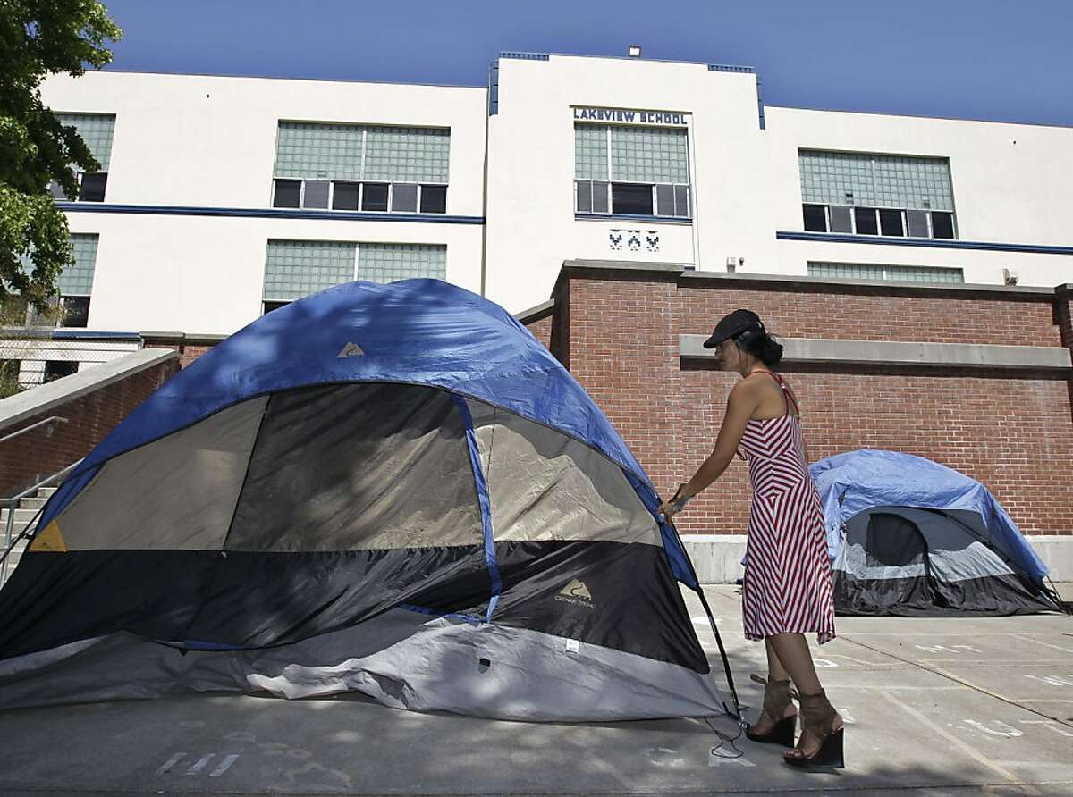 Tina Siu Velasquez straightens up her tent inside of closed Lakeview Elementary School in Oakland, Calif., Tuesday, June 19, 2012 during a protest against school closures. Oakland school district police officers posted notices Monday, the fourth day of the protest, ordering the roughly dozen students, parents and activists on the grounds of Lakeview Elementary School to vacate the premises.