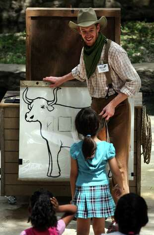 Dru Barcus explains branding to a young visitor at  the Witte Museum.  Photo: Bob Owen, San Antonio Express-News / © 2012 San Antonio Express-News