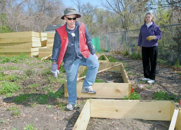 Volunteer Gary Masouredis, left, helps with the placement of a raised garden bed at the Armstrong Court Community Garden in Chickahominy this spring. In the background is volunteer Jane Marsh of Greenwich. Gardeners and volunteers gathered together to start the process of opening the garden for the season. Photo: Bob Luckey / Greenwich Time