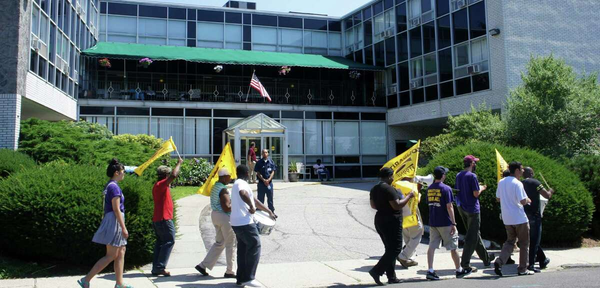Union workers walk a picket line Tuesday in front of the Westport Health Care Center on Post Road West at Burr Road.