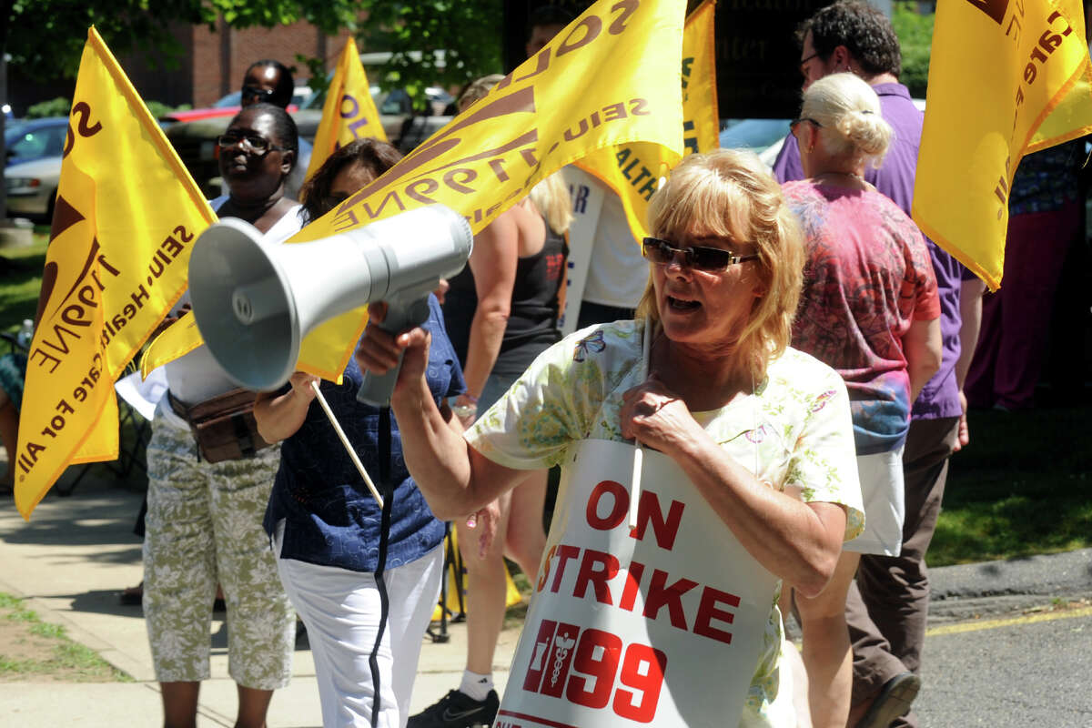 Cynthia Bain, of Milford, and other health care workers protest in front of West River Health Care Center, in Milford, Conn., July 3rd, 2012. Workers at five HealthBridge-owned nursing homes around the state went on strike Tuesday morning after the health care company declined to return to the bargaining table.