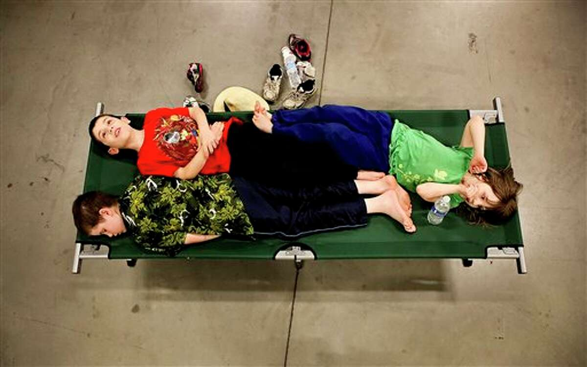 Andrew Tillman, 12, bottom left, Alan Tillman, 9, middle, and Caithlin Tillman, 7, lay on a cot in a Red Cross overnight shelter at the Roanoke Civic Center Special Events Center in Roanoke, Va. The family was spending the night at the cooling center after high temperatures forced them to leave their house, which has been without power since Friday. Nearly three full days after a severe summer storm lashed the East Coast, utilities warned that many neighborhoods could remain in the dark for much of the week, if not beyond.