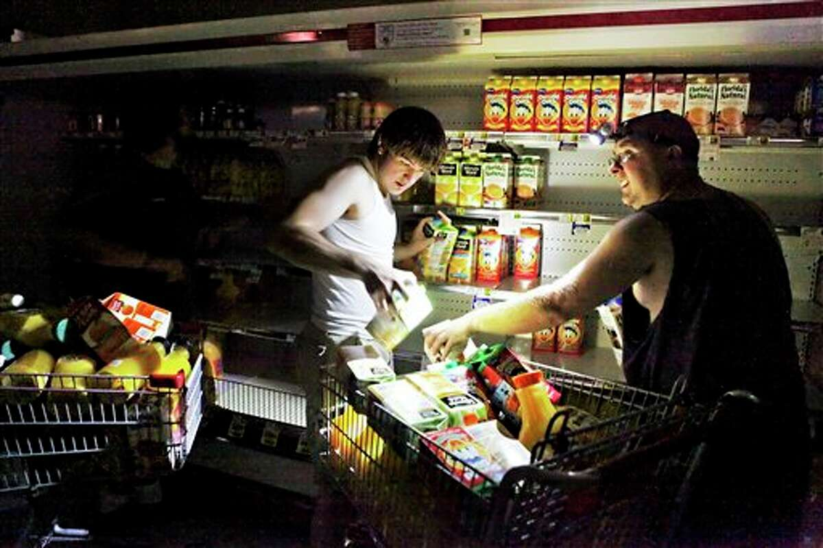 David Robertson and Steve Jones fill their shopping cart with juice at the Mick-or-Mack IGA grocery store in New Castle, Va. Weekend storms killed 10 and left more than 424,000 electricity customers still without power Monday afternoon, nearly three days after the first wave cut through the state.