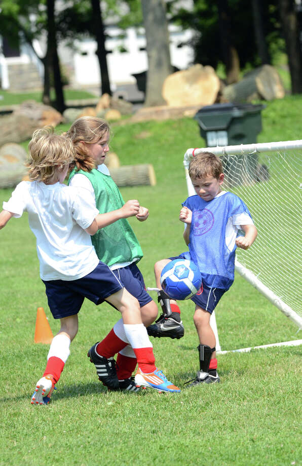 Jack Farrar, 10, of Rowayton, in white, takes a shot on goal keeper Jack Coleman, 7, of Rowayton, in blue pinnie as teammate Ella Murphy, 11, of Darien, assists in the defense during the Packer Soccer Camp at Rowayton Elementary School on Friday, June 29, 2012. The camp is led by Dick Packer, a member of the 1956 Olympic soccer team. Photo: Amy Mortensen / Connecticut Post Freelance