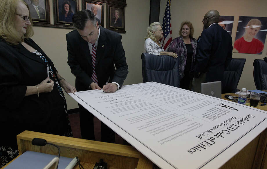 Newly-appointed NISD superintendent Dr. Brian Woods (second from left) signs the Northside ISD Code of Ethics along with other board members during a board meeting on Tuesday, June 26, 2012. Woods replaces outgoing Dr. John M. Folks who has served as superintendent for NISD for nearly a decade before announcing his retirement back in December 2011. Photo: Kin Man Hui, San Antonio Express-News / ©2012 San Antonio Express-News
