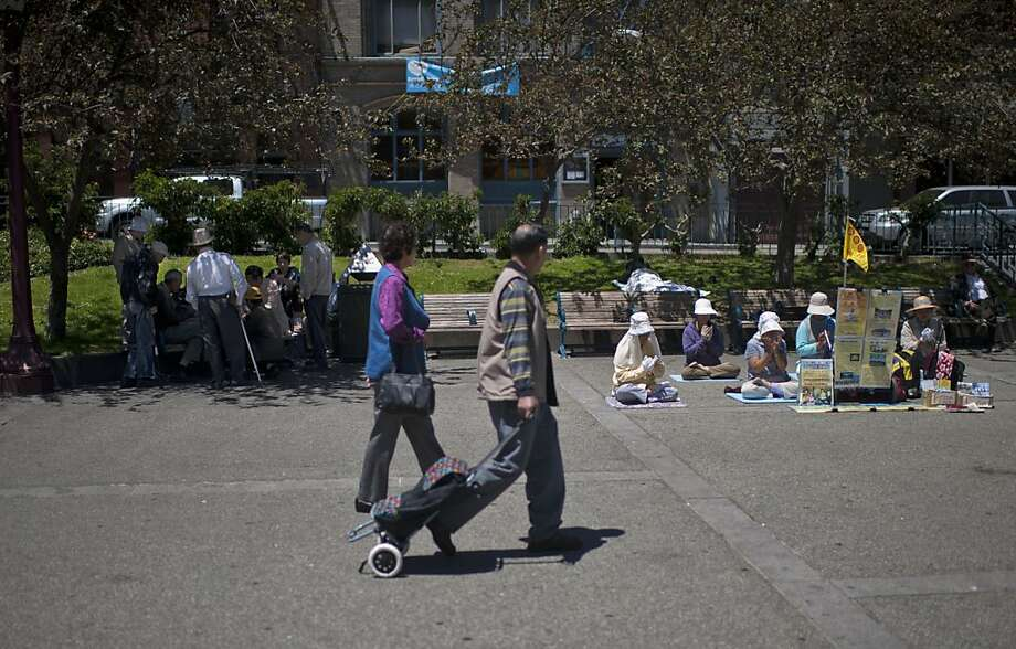 People play cards game, left, and practice Falun Gong at Portsmouth Square, which is located at Clay and Washington Streets north to south and Kearny Street and Walter U. Lum Place east to West, on Wednesday, June 27, 2012 in San Francisco, Calif. Photo: Yue Wu, The Chronicle