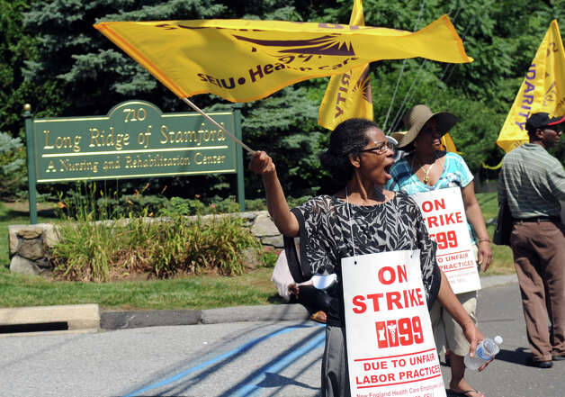 Mary Phitron, left, waves a flag after a driver honked in support of the union as they picket outside Healthbridge's Long Ridge of Stamford nursing and rehabilitation facility in Stamford on Tuesday, July 3, 2012. Photo: Lindsay Niegelberg / Stamford Advocate