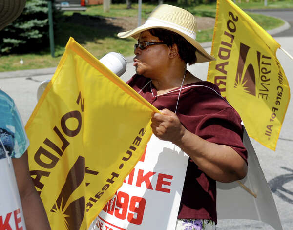 Certified Nursing Assistant Katie Joseph leads the changts as she pickets outside Healthbridge's Long Ridge of Stamford nursing and rehabilitation facility in Stamford on Tuesday, July 3, 2012. Photo: Lindsay Niegelberg / Stamford Advocate