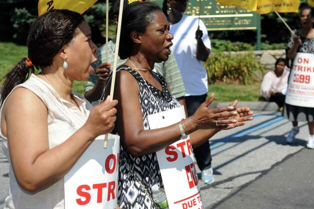 Marie Adelson, left, and Mayfair Pierre, right, both nurses, picket outside Healthbridge's Long Ridge of Stamford nursing and rehabilitation facility in Stamford on Tuesday, July 3, 2012. Photo: Lindsay Niegelberg / Stamford Advocate